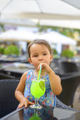 Little girl is drinking  lemonade with mint using straw — Stock Photo