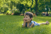 Cute little girl laying in the grass on a sunny summer day — Stock Photo