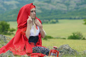 Beautiful blonde woman in old-fashioned dress and red cloak sitting on the meadow — Stock Photo