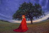 Beautiful blonde woman in old-fashioned dress and red cloak sitting under an oak — Stock Photo