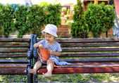 Trendy little girl sitting on a wood bench with her handbag — Stock Photo