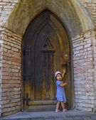 Little girl near the old fashioned door — Stock Photo