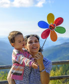 Summer holidays, family, children and people concept - happy mother and child girl with pinwheel toy — Stock Photo