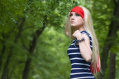 Blonde girl with red scarf and striped dress in the forest — Stock Photo