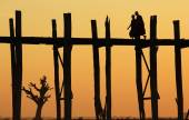 Monks crossing the U-Bein bridge at sunrise — Stock Photo