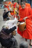 Unidentified Buddhist monks receiving morning alms — Stock Photo