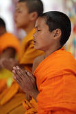 Unidentified praying Buddhist novice in Vat Xieng Thong — Stock Photo