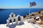 Scenic caldera view with Greek flag in Oia — Stock Photo