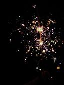 Girl hand, holding a burning sparkler — Stock Photo