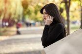 美しい女性を公園のショッピング バッグと電話で話す — ストック写真