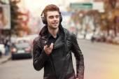 Man in headphones on the street. Standing with phone in hand — Foto de Stock