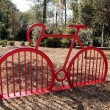 Red bike rack in a park shaped like a bike. — Stock Photo #55839305