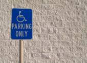 Blue handicap parking sign with a white textured concrete block background that can be used for copy space. — Stock Photo