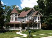 New two story Victorian residential home with vinyl or board siding on the facade styled after an old-fashioned historical house with bay windows, gingerbread and a turret. — Stock Photo