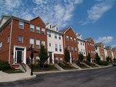 A row of brick condos or townhouses beside a street. — Stock Photo