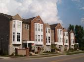 A row of brick condos or townhouses with bay windows beside a street. — Stock Photo