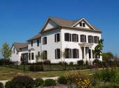 Two story new home built to look like an old historical home complete with the added on look, painted brick and a wrought  iron fence. — Stock Photo