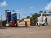 Outside view of a south Georgia lumber yard with blue silos and stacks of fresh cut green lumber curing in the sunshine with a forklift moving pallets. — Stock Photo