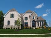 New two story white brick and stone residential home with turret and side garage. — Stock Photo
