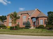 Large two story new red brick residential home with a turret at the corner. — Stock Photo