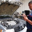 Auto mechanic performing a routine service inspection in a service garage. — Stock Photo #56963137