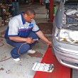 Auto mechanic inspecting a cars tire pressure in a service garage. — Stock Photo #56963143