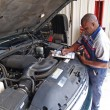 Auto mechanic performing a routine service inspection in a service garage. — Stock Photo #56963177