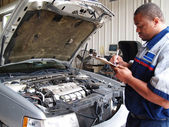 Auto mechanic performing a routine service inspection in a service garage. — Fotografia Stock