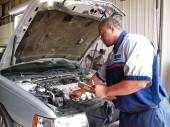 Auto mechanic checking radiator levels while performing a routine service inspection in a service garage. — Stock Photo