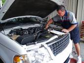 Auto mechanic performing a routine service inspection in a service garage. — Stockfoto