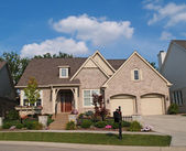 Small beige brick home with a two car garage in the front. — Foto Stock