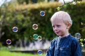 One Little boy blows soap bubbles in the garden on a summer day — Stock Photo