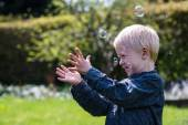 One Little boy blows soap bubbles in the garden on a summer day — 图库照片