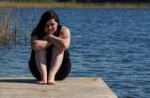 Young Woman sitting meditating on the Jetty — Foto Stock