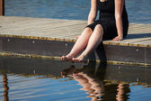 Young lady sitting on the jetty  — Foto de Stock