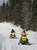 Two snowmobilers riding on a groomed snowmobile trail near Waskesiu in Central Saskatchewan. — Stok fotoğraf
