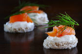 Canapes with salmon, cream and dill garnish, on dark brown wood, — Stock Photo