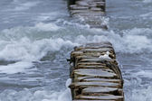 Wooden breakwater and waves with foam at the sea — Stock Photo