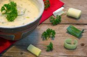 Creme sauce in a bowl with fresh leeks and herbs on  rustic wood — Stock Photo