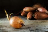 Onions on rustic wood, dark background — Stock Photo