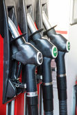 Gas pump nozzles in a service station — Stock Photo