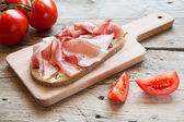 Hearty bread with ham  bacon  on a wooden board — Stock Photo