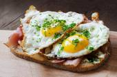 Slice of rustic bread with ham  and fried eggs — Stock Photo
