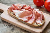 Country bread with smoked ham bacon on a wooden board — Stock Photo