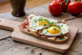 Country bread with ham and fried egg on a rustic table — Stok fotoğraf