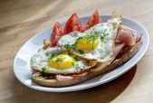 Bread with ham and fried egg garnish with chives on a plate — 图库照片