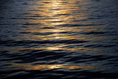 Holiday background, sunset reflections on calm sea waves — Stockfoto