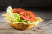 Bread roll with cheese, salad and tomatoes on  rustic wood, dark — Stock Photo