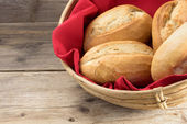 Bread rolls in a basket whith red napkin on old wood — Stock Photo