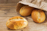 Bread rolls in a paper bag on a rustic wooden table — Stock Photo